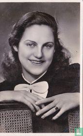 Jonge vrouw met strik leunend op rieten stoel