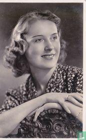 Jonge vrouw met sieraden leunend op houten stoel