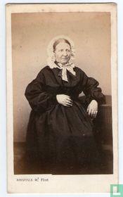 Vrouw in traditionele kledij aan tafel