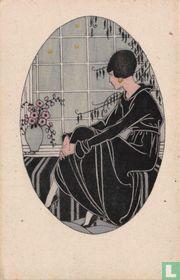 Vrouw in zwarte jurk zit voor raam